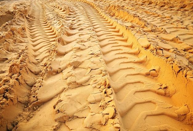 砂の上のタイヤ跡。砂の上の車輪の痕跡