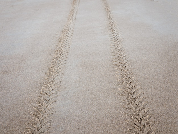 Tire tread mark on the sea sand extending into the distance.