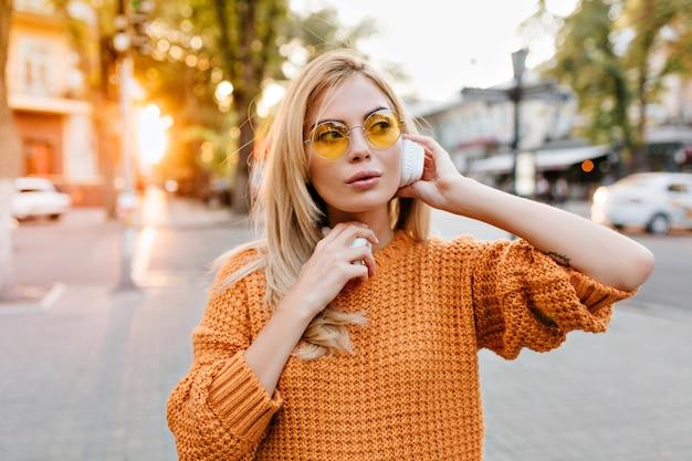 Усталая очаровательная дама в оранжевом свитере стоит на городской площади и слушает любимую песню в наушниках