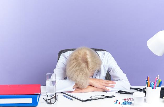의료 가운을 입은 피곤한 성인 여성 의사는 사무실 도구를 들고 책상에 앉아 복사 공간이 있는 보라색 벽에 격리된 책상에 머리를 얹고 있습니다.