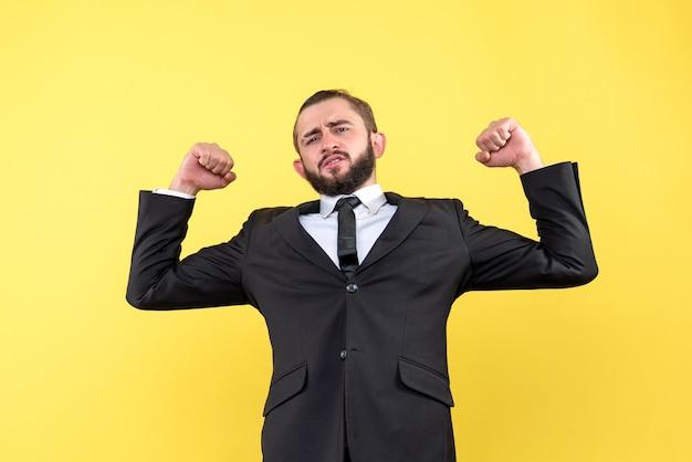 Усталый взрослый хмурится в костюме на желтом фоне