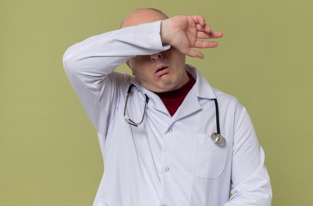 의사 제복을 입은 피곤한 성인 남자가 이마에 팔을 얹고 청진기를 들고 있다