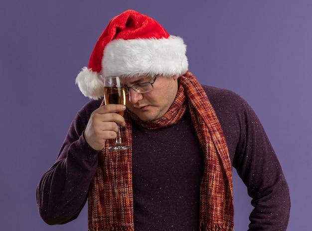 Uomo adulto stanco con gli occhiali e cappello da babbo natale con sciarpa intorno al collo che tocca la fronte con un bicchiere di champagne con gli occhi chiusi, isolato su sfondo viola