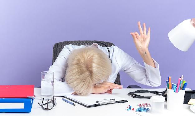 Stanco adulto slava dottoressa in veste medica con stetoscopio seduto alla scrivania con strumenti da ufficio mettendo la testa sulla scrivania e gesticolando segno ok isolato su sfondo viola con spazio di copia