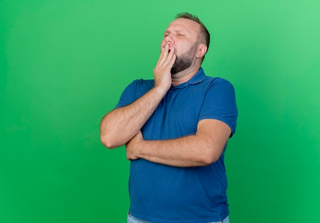 Tired adult slavic man putting hand on mouth yawning with closed eyes isolated on green wall with copy space