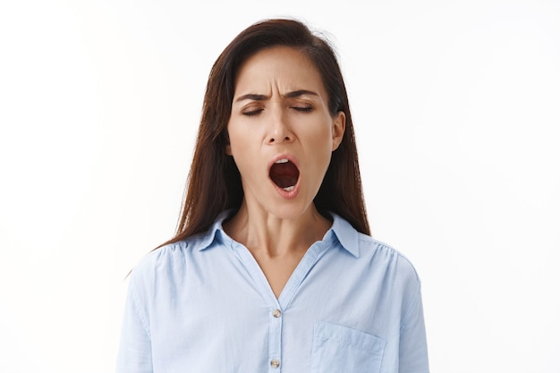 Tired adult woman hardworking businesswoman stay late work, yawning tired, close eyes open mouth wide, feeling sleepy drained, want sleep, wake up early morning, stand white wall