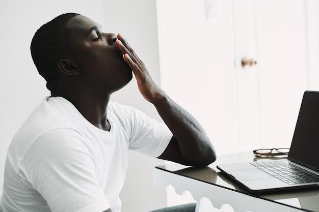 노트북 작업 사무실과 함께 실내 테이블에 피곤된 아프리카 남자
