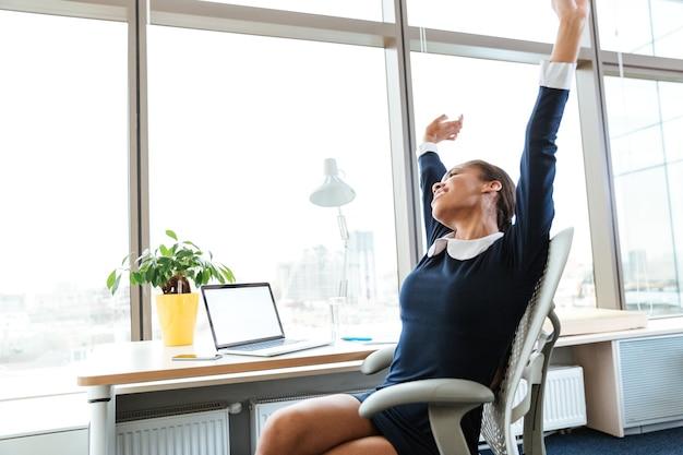 手を上げてオフィスでストレッチしながら窓の近くのテーブルのそばに座っているドレスを着た疲れたアフロビジネスウーマン。