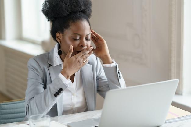 직장에서 하품하는 블레이저를 입은 피곤한 아프리카 사무실 직원, 만성 피로, 지루한 직업으로 고통받습니다.