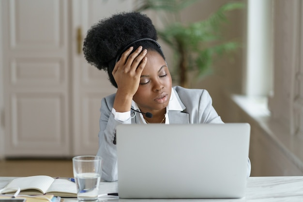 Tired afro office employee with headphones sleeps in the workplace, suffering from chronic fatigue
