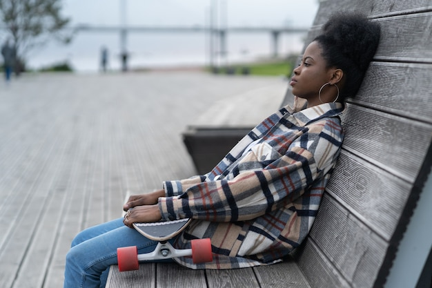 Tired afro skateboarder girl sitting alone on bench in urban open space depressed ponder outdoors
