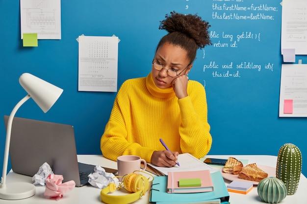 疲れたアフロの学生は、ラップトップコンピューターでウェビナーやチュートリアルをオンラインで注意深く見、自分のキャビネットで勉強し、公開記事を準備します