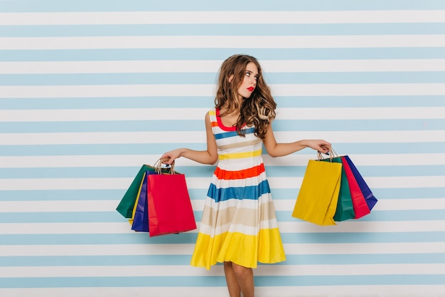 Tired after long shopping girl posing on  wall of striped wall with funny displeased face. portrait of young attractive girl in bright outfit.