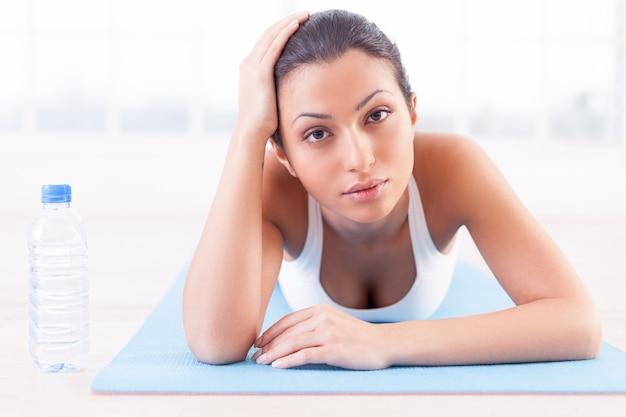 Устал после тренировки. усталая молодая индийская женщина, лежа на коврике для йоги и глядя в камеру
