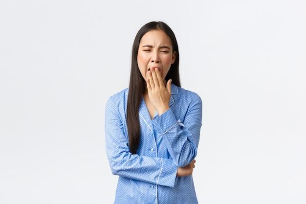 寝坊パーティーで退屈な話からあくびをしている青いパジャマで疲れて退屈なかわいいアジアの女の子、疲れ果てて、興味の欠如を示して、白い背景の上に立って眠りたい