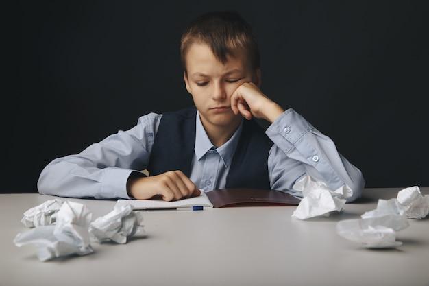 Усталый и подавленный школьник сидит за партой и учится в одиночестве.