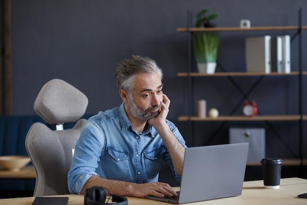 ラップトップを持ってホームオフィスで働いている疲れて失望した年配の男性。