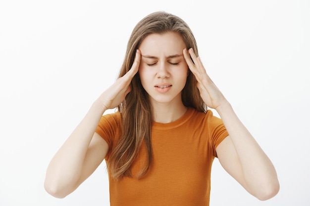 Усталая и расстроенная привлекательная девушка массирует виски и закрывает глаза, страдает головной болью, не может сосредоточиться на домашней работе