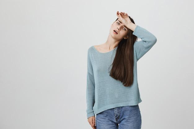 Уставшая и расстроенная женщина вытерла лоб от пота, измученная
