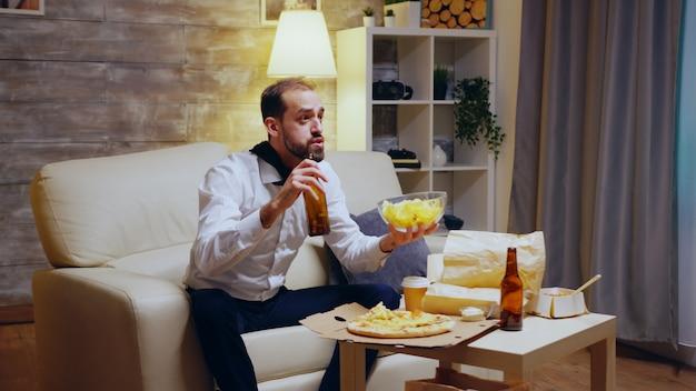 Усталый и взволнованный предприниматель с галстуком ест чипсы и смотрит спортивные передачи по телевизору.