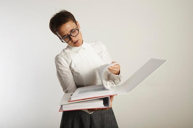 Усталая и хмурящаяся молодая учительница в консервативной одежде и черных круглых очках переворачивает страницы в толстой папке на белом