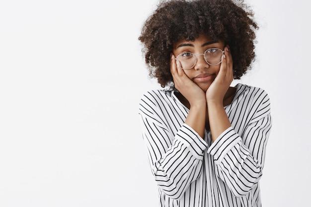 Усталая и мрачная, безразличная смуглая молодая девушка с афро-прической, сжимающая лицо ладонями на щеках, беззаботно уставившаяся и измученная, мечтающая о выходном