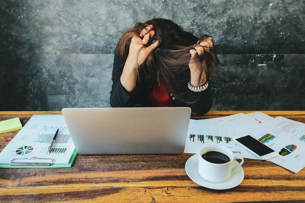 Устал и головная боль деловая женщина в офисе с помощью ноутбука и анализа инвестиционных графиков на бумаге для документов