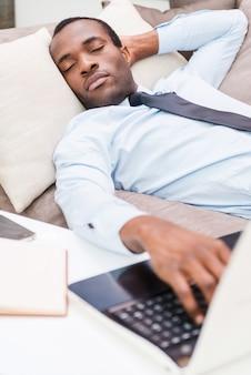 피곤하고 과로. 노트북 키보드에 손을 잡고 formalwear에서 잘 생긴 젊은 아프리카 남자
