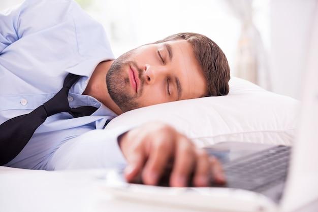 Устал и перегружен работой. красивый молодой человек в рубашке и галстуке спит в постели, положив руку на клавиатуру ноутбука