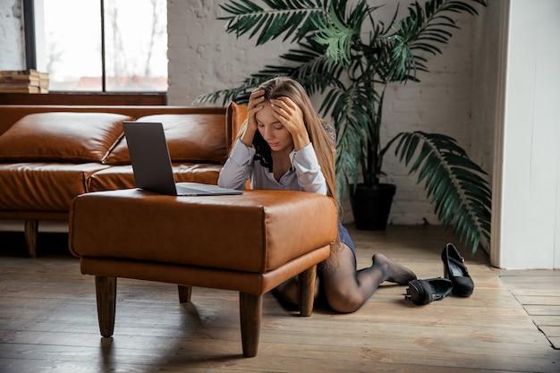 Усталая и напряженная элегантная деловая женщина, работающая дома, снимает обувь, держит ее после тяжелого рабочего дня. фото высокого качества