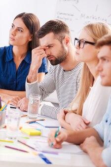 Устал и в стрессе. подавленный молодой человек трогает лицо рукой, сидя за столом вместе со своими коллегами