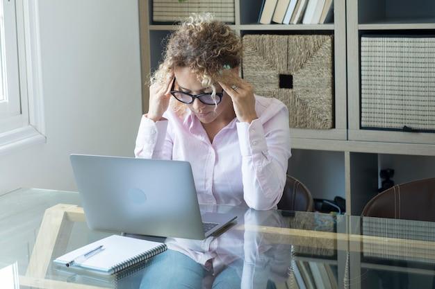 집에서 컴퓨터 작업을 하는 피곤하고 스트레스를 받는 사람들 - 똑똑한 작업의 개념과 생각과 문제에 대해 머리를 만지는 현대 여성 - 건강에 해로운 사무실 노트북 자세 개념