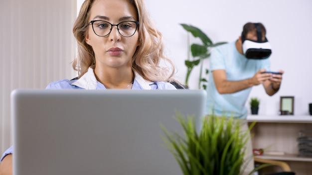 남편이 백그라운드에서 vr 헤드셋으로 비디오 게임을 하여 그녀를 방해하는 동안 피곤하고 화가 난 프리랜서 여성은 집에서 컴퓨터 노트북 작업을 하고 있습니다.