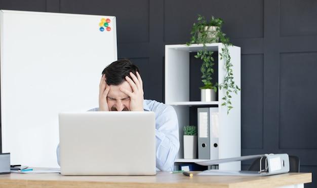 Усталый и обеспокоенный деловой человек на рабочем месте в офисе, взявшись за голову руками