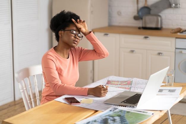 疲れた建築家の女性が自宅で仕事をする額黒のフリーランサーの女性が頭痛に苦しんでいる