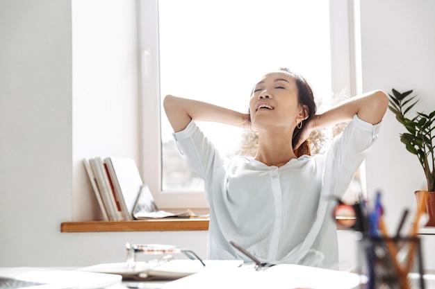 オフィスのテーブルのそばに座って目を閉じてリラックスして疲れたアジアのビジネス女性