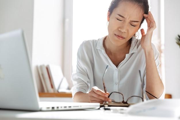 オフィスのテーブルのそばに座っている間頭痛を持っている彼女の寺院に触れる疲れたアジアのビジネスウーマン