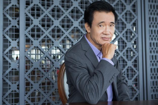 Tired asian businessman sitting in restaurant