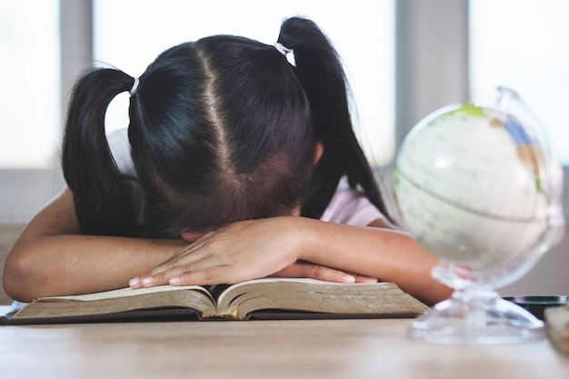 Tired asian little child girl sleeping over the opened book in the classroom