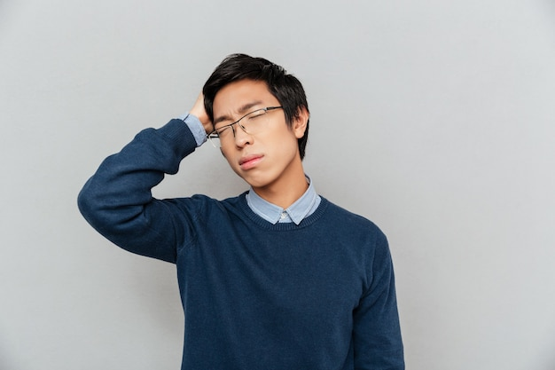 피곤 된 아시아 사람. 눈을 감다