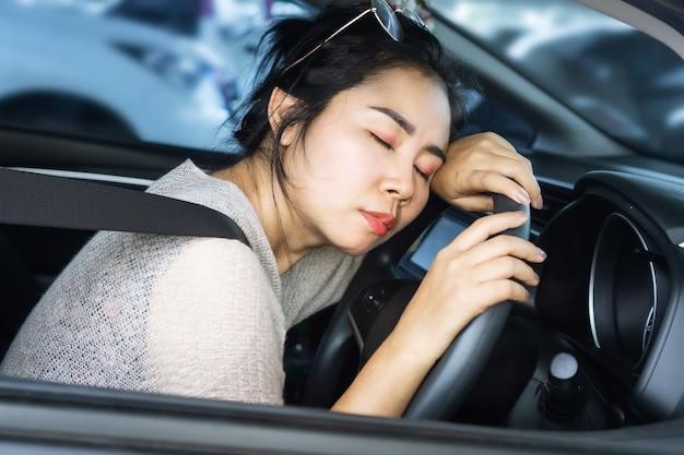車の安全第一の概念で眠っている疲れたアジアの女性