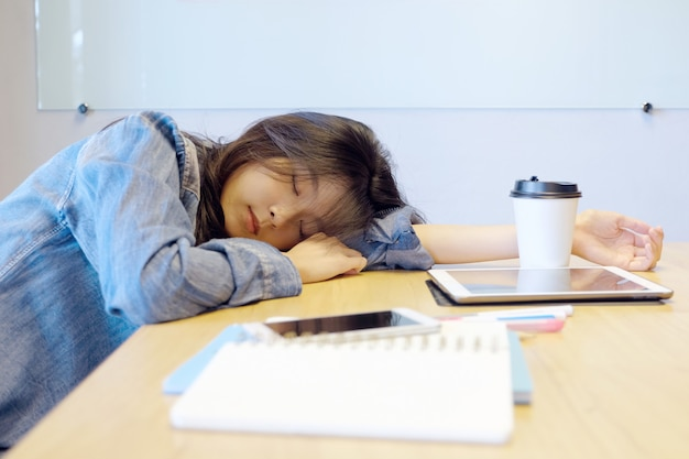 Tired asian woman sleeping at office desk.
