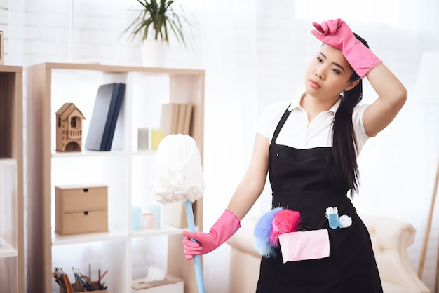 Tired asian woman works housekeeper with mop.