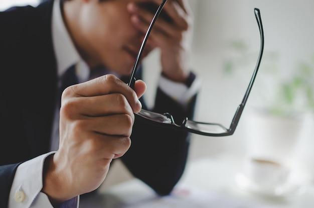 Утомленный азиатский молодой бизнесмен чувствуя усиленный и снимая eyeglasses чувствует усталость глаза усталость после длинной работы офиса