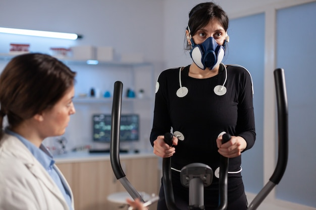 Tired athlete woman training on cross trainer increasing, rhythm of exercises wearing mask and medical electrodes monitoring muscle endurance and cardiac rate in science sport laboratory.