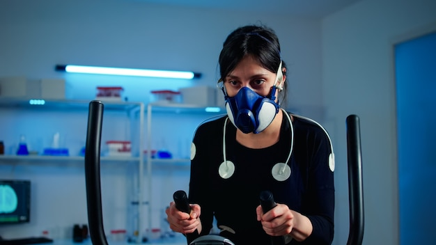 Tired athlete woman training on cross trainer increasing rhythm of exercises wearing mask and medical electrodes monitoring muscle endurance and cardiac rate in science sport laboratory