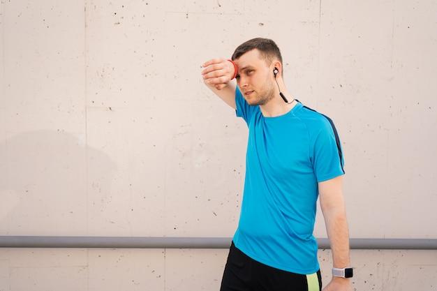 Усталый спортивный человек вытирает пот на лбу