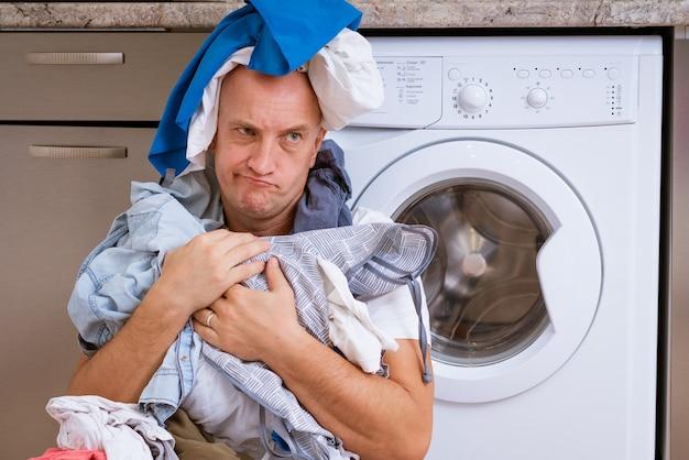 Усталый лысый мужчина сидит с грязным бельем в стиральной машине