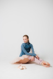 Tired ballerina is sitting on the floor on a white background