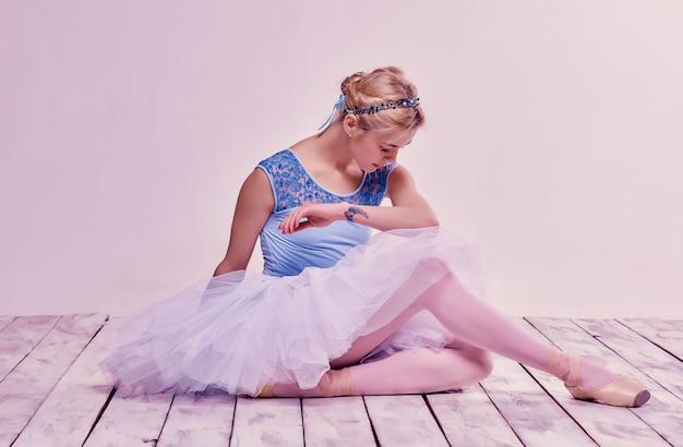 Утомленная балерина сидит на деревянном полу